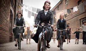 Well-dressed mid-century midwives on bikes